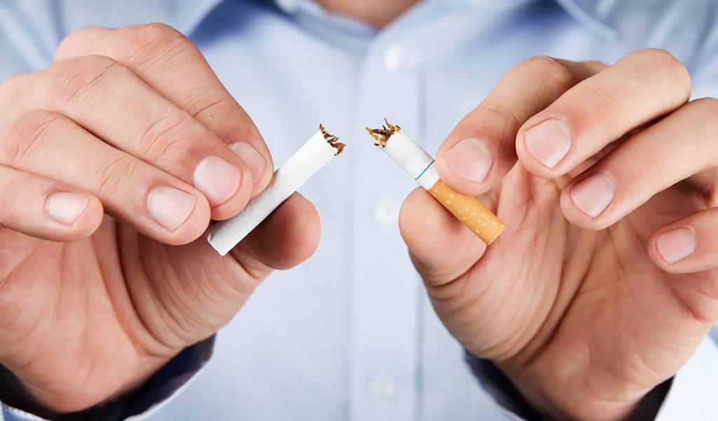 Hände zerbrechen eine Zigarette