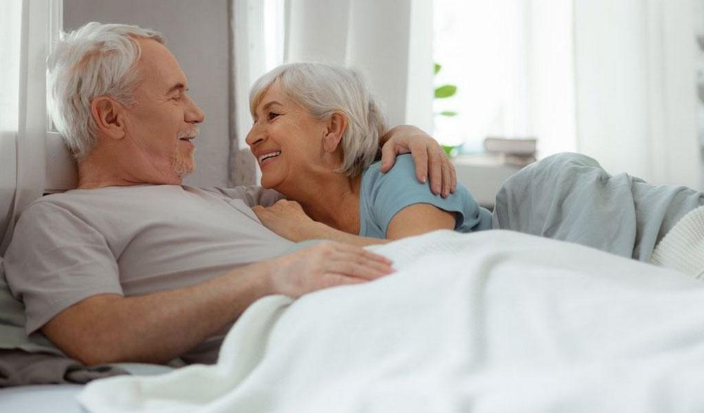 Älteres Paar kuschelt im Bett