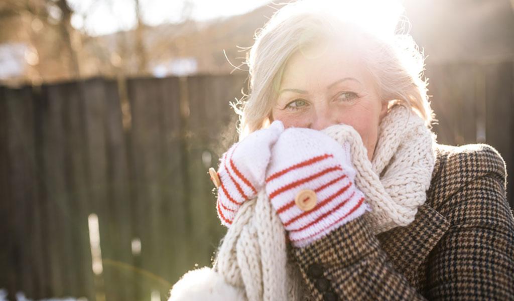 Frau hält sich einen Schal vor das Gesicht