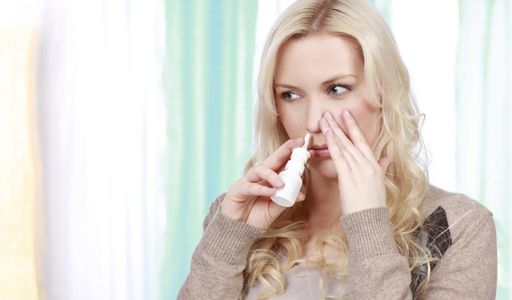 Blonde Frau benutzt ein Nasenspray