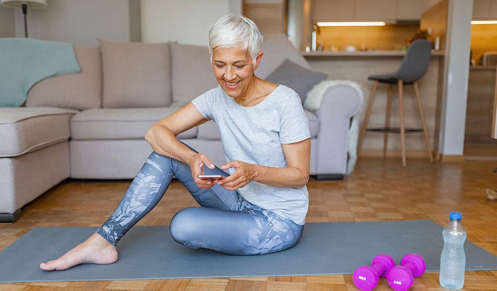 Frau sitzend auf Yogamatte mit einem Handy in der Hand