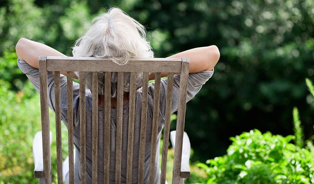 Frau im Garten sonnt sich