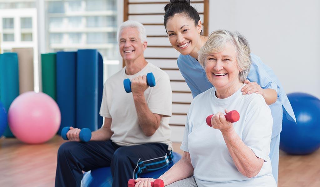 Fitnesstrainerin mit Seniorenpaar im Fitnessraum