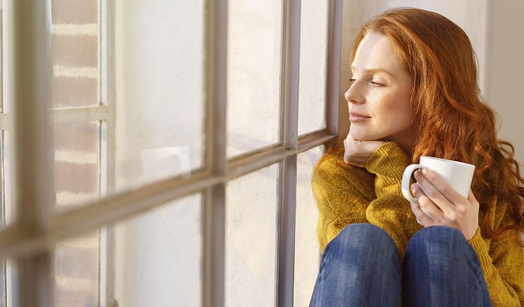 Tee trinkende Frau am Fenster zur kalten Jahreszeit