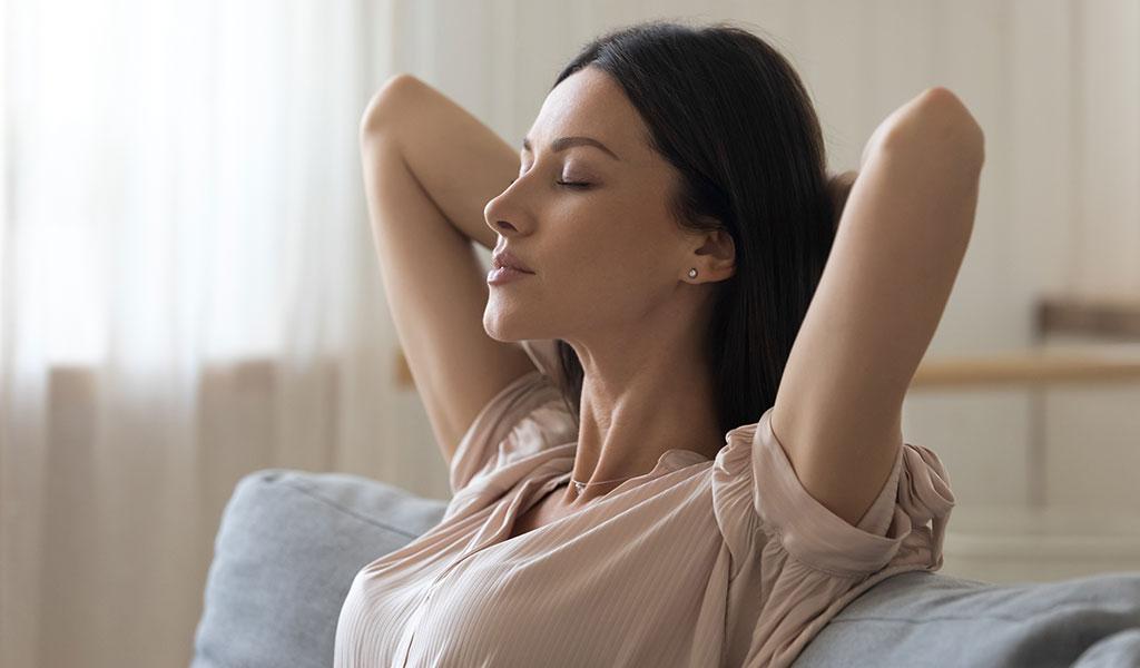 Junge Frau entspannt auf Sofa mit geschlossenen Augen